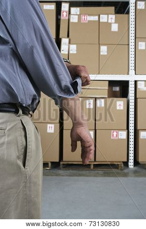 Close up of businessman rolling up his sleeve in warehouse