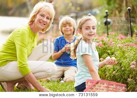 Grandmother With Grandchildren On Easter Egg Hunt In Garden