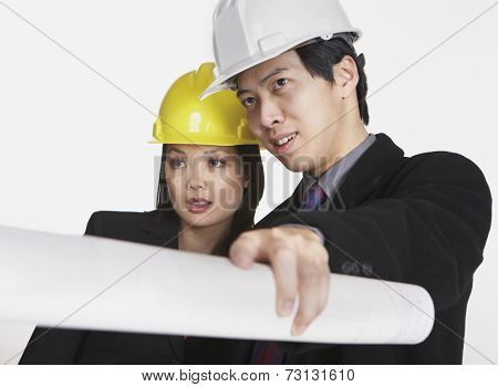 Studio shot of Asian businesspeople wearing hard hats