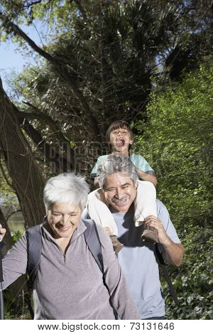Hispanic grandparents and grandson on nature walk