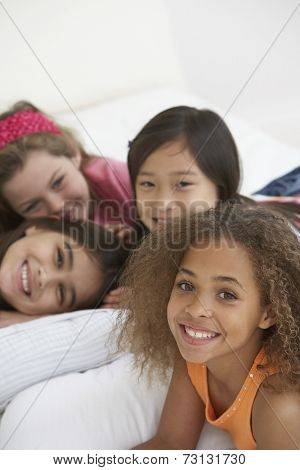 Group of young girls lying on bed