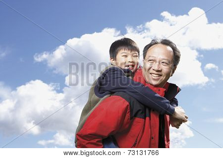 Asian father giving son piggyback ride outdoors