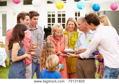 Multi Generation Family Celebrating Birthday In Garden