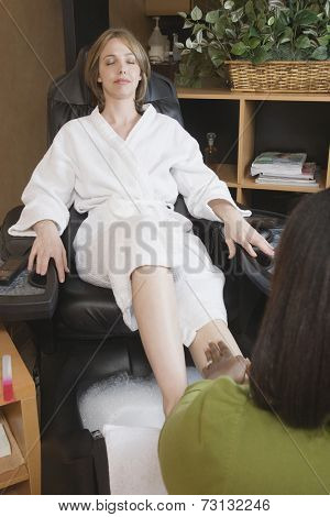 Woman receiving spa pedicure