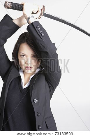 Studio shot of Asian businesswoman holding sword