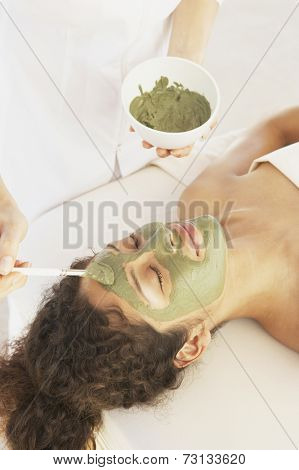 Woman on massage table getting facial treatment