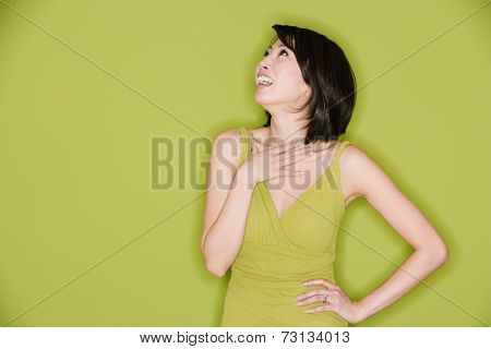 Studio shot of Asian woman looking up and laughing