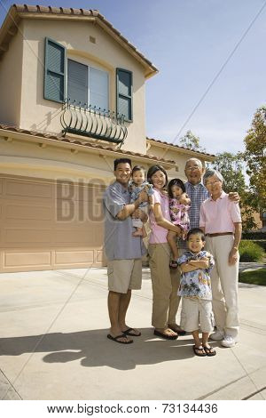 Multi-generational Asian family in driveway