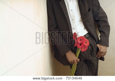 African American man in suit holding flowers