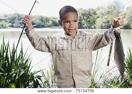 Young African boy with fishing pole and fish