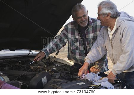 Two senior men working under hood of car