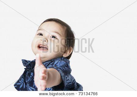 Studio shot of toddler boy reaching