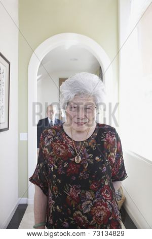 Senior Asian woman smiling in hallway
