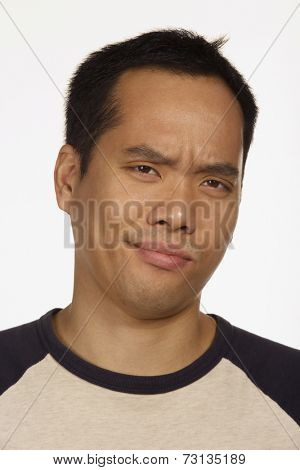 Close up studio shot of Asian man looking skeptical