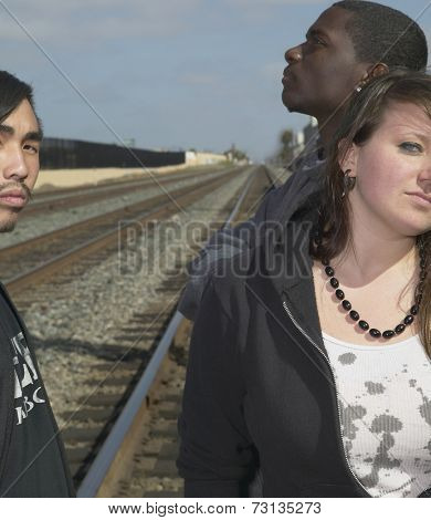 Group of young adults standing on railroad tracks
