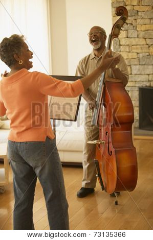 Senior African couple singing and playing upright bass