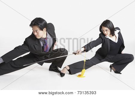 Studio shot of Asian businesspeople with swords