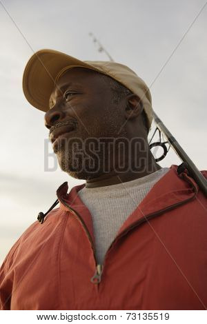 Low angle view of African man holding fishing pole