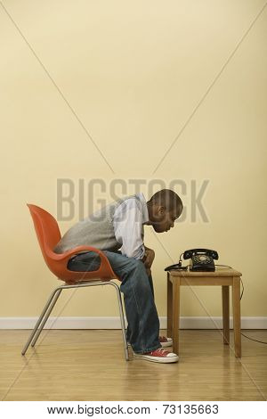 African man staring at telephone