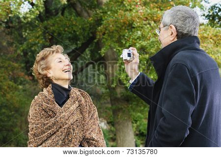 Senior man talking senior woman's photograph outdoors