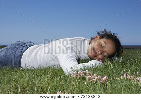 African woman laying in grass with eyes closed