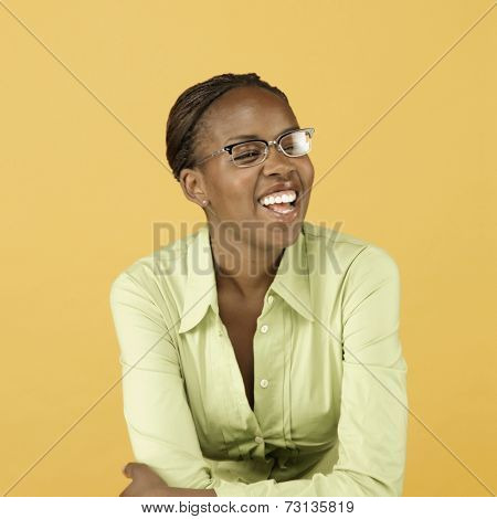 Studio shot of African woman wearing eyeglasses and smiling