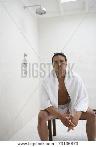 Man wearing towel and underwear in bathroom