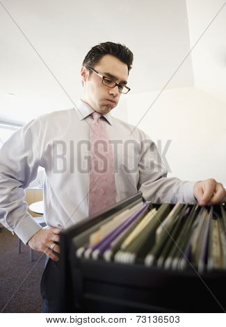 Businessman sorting through file cabinet