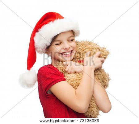 christmas, x-mas, winter, happiness concept - smiling girl in santa helper hat with teddy bear