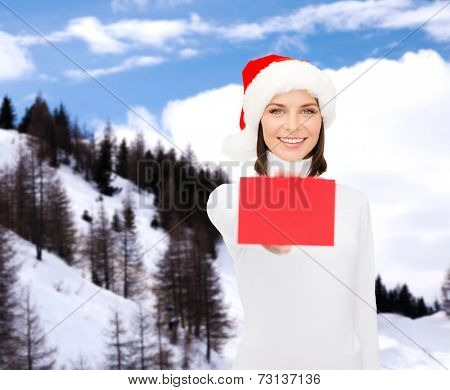 christmas, holdays, people, advertisement and sale concept - happy woman in santa helper hat with blank red card over snowy mountains background