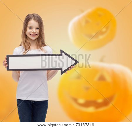advertising, direction, holidays and people concept- smiling little girl holding big white arrow over halloween pumpkins background
