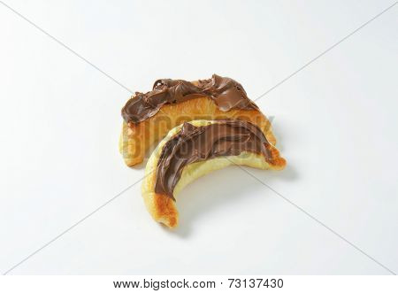 overhead view of two croissants with chocolate spread