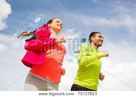 fitness, sport, friendship and lifestyle concept - smiling couple with earphones running outdoors