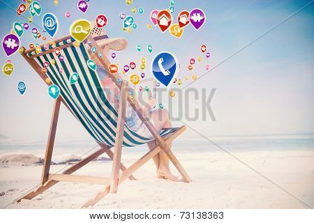 Woman in sunhat sitting on beach in deck chair using tablet pc with colourful computer applications