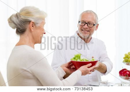 family, holidays, thanksgiving, christmas and people concept - smiling senior couple having dinner at home