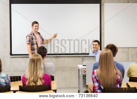 education, high school, technology and people concept - smiling student boy with remote control, laptop computer standing in front of white board and teacher in classroom