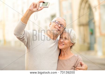 age, tourism, travel, technology and people concept - senior couple with camera taking selfie on street