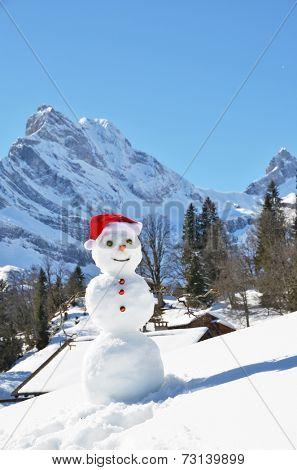 Snowman against Alpine panorama. Switzerland