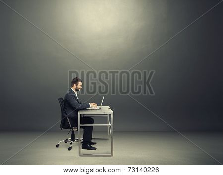 sideview of smiley young businessman sitting at the table and working with laptop in the dark room with empty copyspace