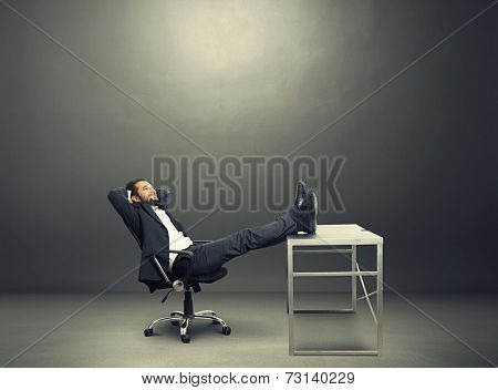 young businessman put his feet up on the table, resting and smiling. photo in the dark room