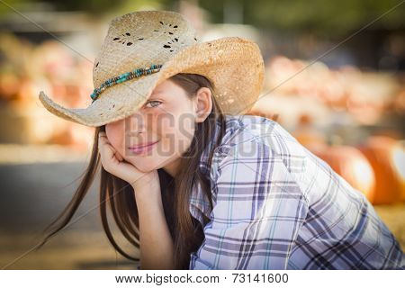 Pretty Preteen Girl Wearing Cowboy Hat Portrait at the Pumpkin Patch in a Rustic Setting.