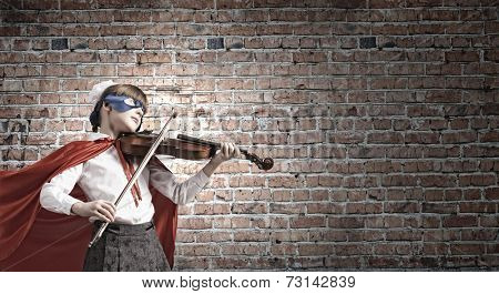 Cute girl of school in superhero costume playing violin