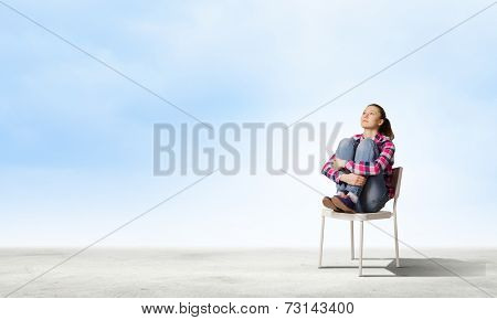 Young girl sitting in chair against city background