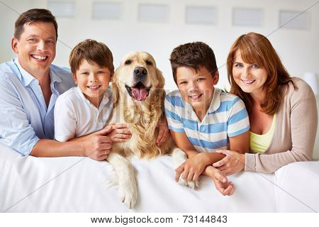 Smiling family with thoroughbred dog looking at camera
