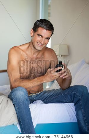 Portrait of shirtless man using cell phone