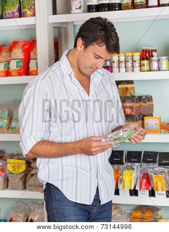 Mid adult man choosing product in grocery store