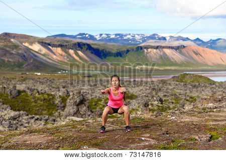 Fitness girl exercising outdoors doing jump squat in amazing nature landscape. Fit female woman athlete cross-training outside. Image from Iceland.