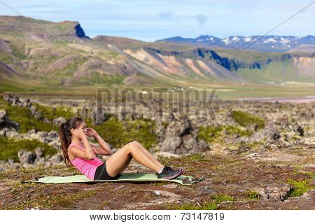 Sit-ups fitness woman doing situps training core outside in amazing nature landscape on Iceland. Fit female sport model girl training crossfit outdoors. Mixed race Asian Caucasian athlete.