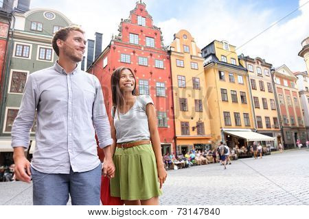 Couple in Stockholm, Sweden, Europe. Happy multiracial young couple walking outside on Stortorget big square in Gamla Stan, the old town of Stockholm. Scandinavian man, Asian woman.