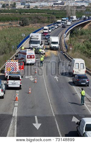 VALENCIA, SPAIN - SEPTEMBER 30, 2014: Police directing traffic around a traffic accident where a small car collided head on with a truck. In 2013, Spain had over 1,900 traffic fatalities.